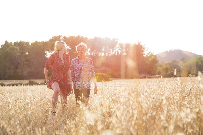 Young woman looking back at boyfriend running in wheat field, Majorca, Spain — Stock Photo