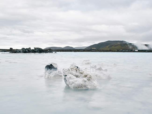 Piscina geotérmica com vista distante montanhas — Fotografia de Stock