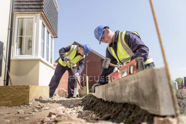 Aprendiz construtores usando escavador para levantar pedras kerb no canteiro de obras de habitação — Fotografia de Stock