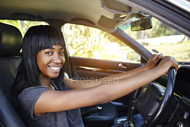 Portrait of young woman driving car — Stock Photo