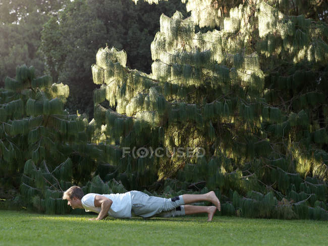 Young man exercising outdoors, doing push-ups — Stock Photo