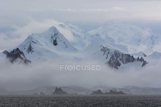 Низкие облака над айсбергов на канале Лемэр, Антарктида — стоковое фото