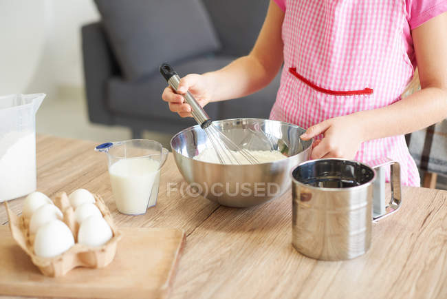 Young girl whisking ingredients together in bowl, mid section — Stock Photo