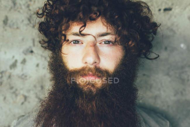 Portrait de jeune homme hipster avec brune cheveux bouclés et la barbe de près — Photo de stock