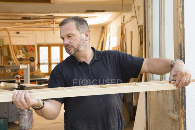 Man quality checking wooden plank — Stock Photo