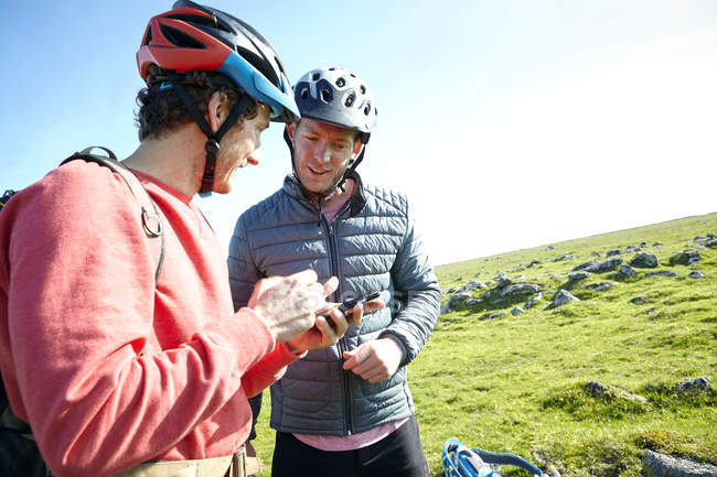 Cyclists on hillside looking at smartphone — Stock Photo