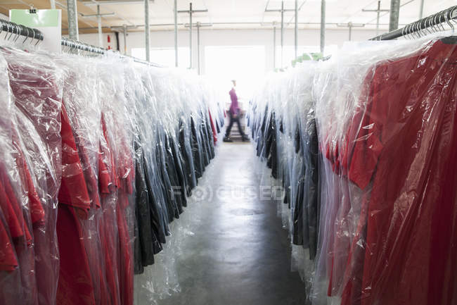 Diminishing perspective of garments on clothes rail in sewing factory — Stock Photo
