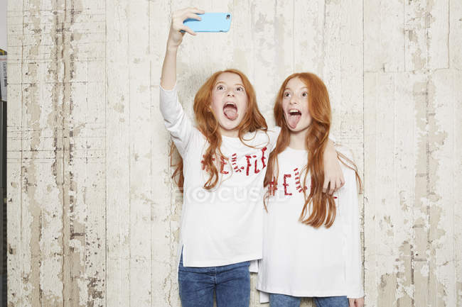 Portrait of twin sisters wearing Christmas jumpers, taking selfie using smartphone — Stock Photo