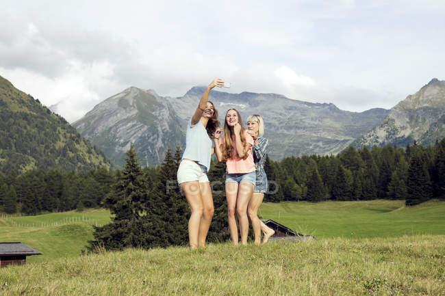 Троє дорослих подруг, що приймають смартфон селфі в австрійських Альпах, Sattelbergalm, Тіроль, Австрія — стокове фото