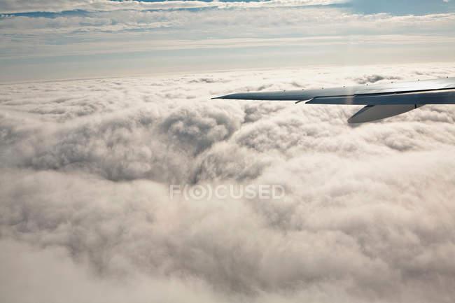 Flugzeugflügel und weiße Wolken — Stockfoto