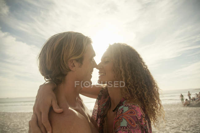 Couple on beach, hugging, face to face, smiling — Stock Photo