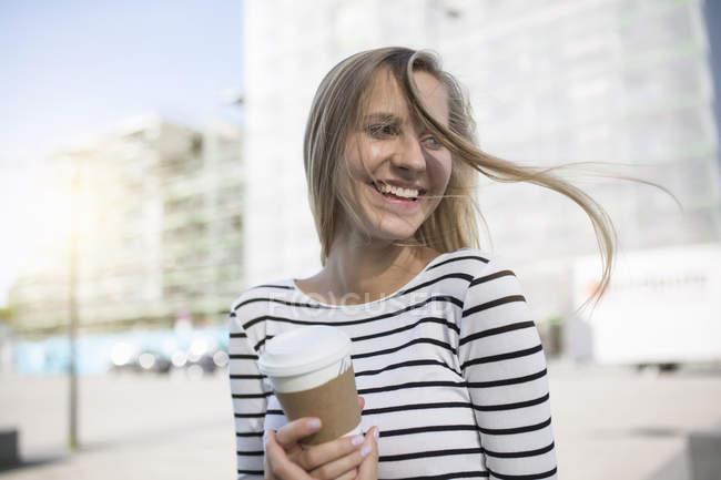 Junge Frau mit blonden Flatterhaaren zum Mitnehmen — Stockfoto