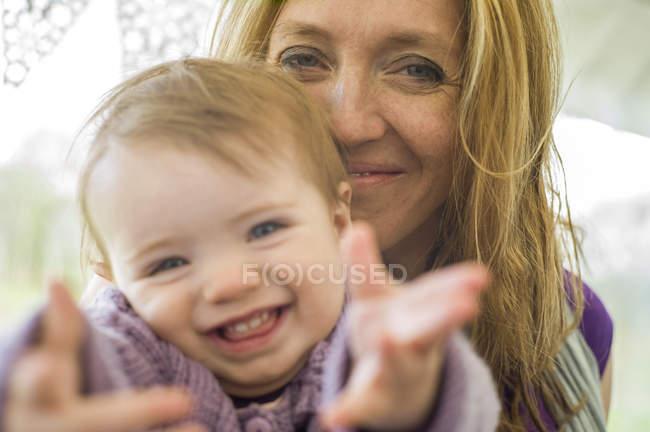 Портрет матері і дочки дивлячись на камеру посміхаючись — стокове фото