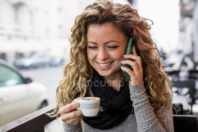 Mulher no café segurando xícara de café fazendo chamada telefônica sorrindo — Fotografia de Stock