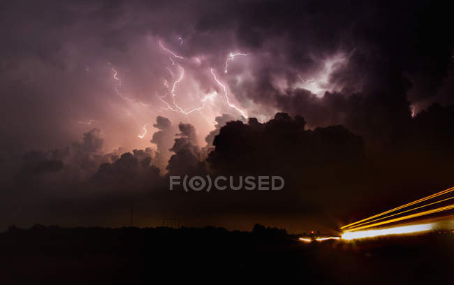 Lightning shoots up the updraft and anvil of tornadic supercell at night with car light trails — Stock Photo