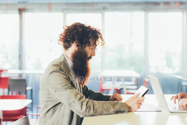 Giovane hipster maschio con capelli ricci e barba con tablet digitale alla scrivania — Foto stock