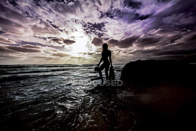 Silhouetted donna sexy in piedi su rocce costiere — Foto stock