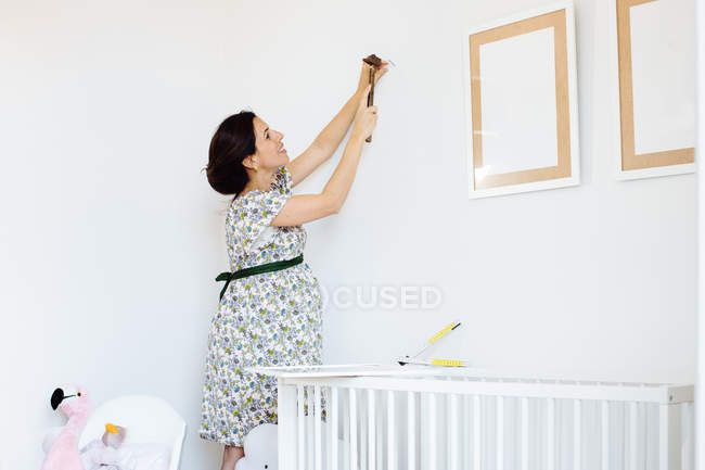 Pregnant mid adult woman hammering nail for picture frame in child nursery — Stock Photo