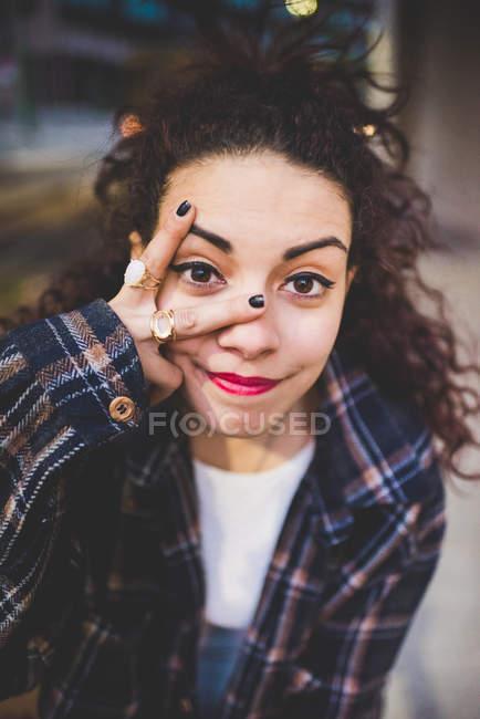 Portrait de femme regardant la caméra entre les doigts — Photo de stock