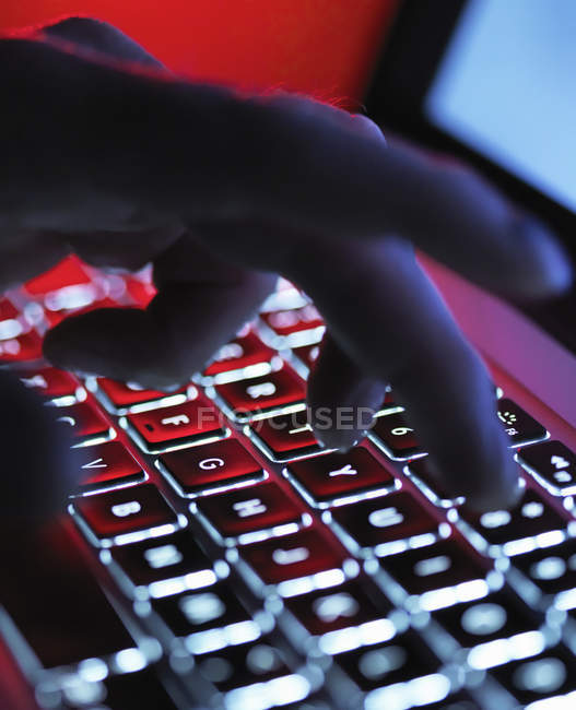 Cropped image of hand typing on laptop computer at night — Stock Photo