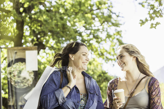 Two women friends with takeaway coffee chatting in park, Franschhoek, South Africa — Stock Photo