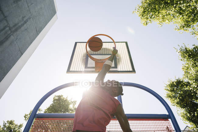 Young male basketball player throwing ball in sunlit basketball hoop — Stock Photo