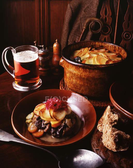 Ciervo estofado con col morada, rebanadas de papas, zanahorias, cebollas y puerros con un vaso de cerveza y pan integral - foto de stock