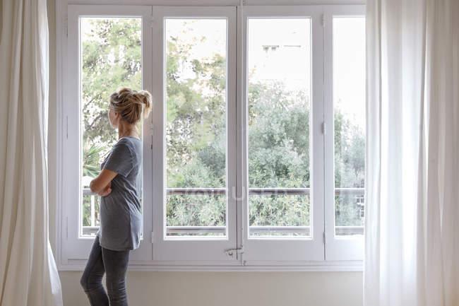 Mulher em casa, olhando pela janela — Fotografia de Stock