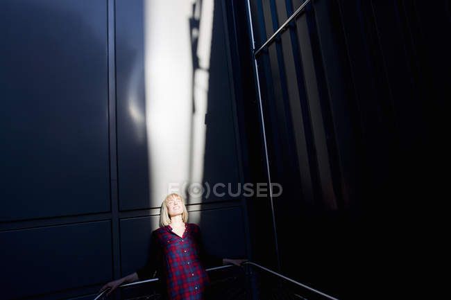 Blond woman basking in sunlight on stairway — Stock Photo