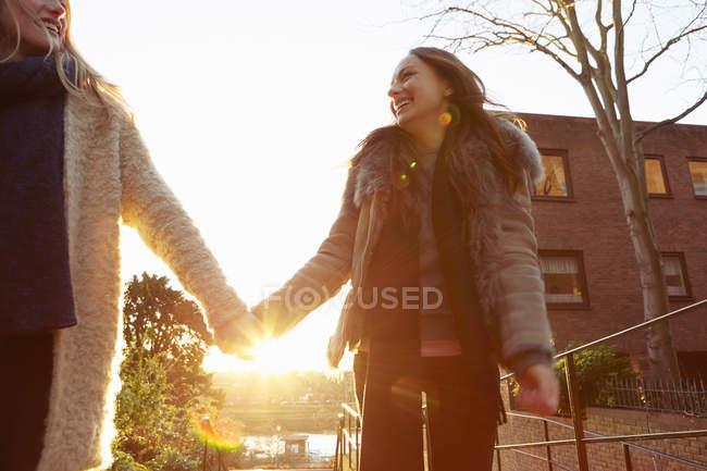 Две подруги идут рука об руку и смеются. — стоковое фото