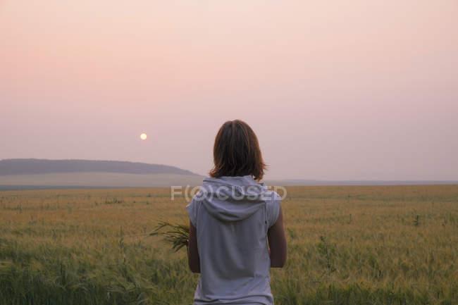 Donna in piedi in campo a guardare il tramonto, vista posteriore, Ural, Russia — Foto stock
