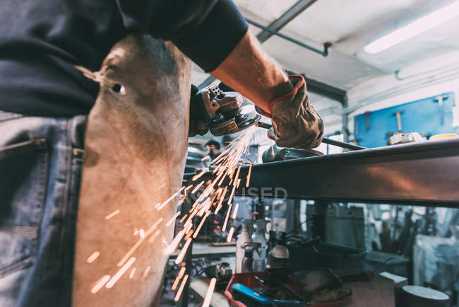 Mid section of metalworker grinding metal rod in forge workshop — Stock Photo