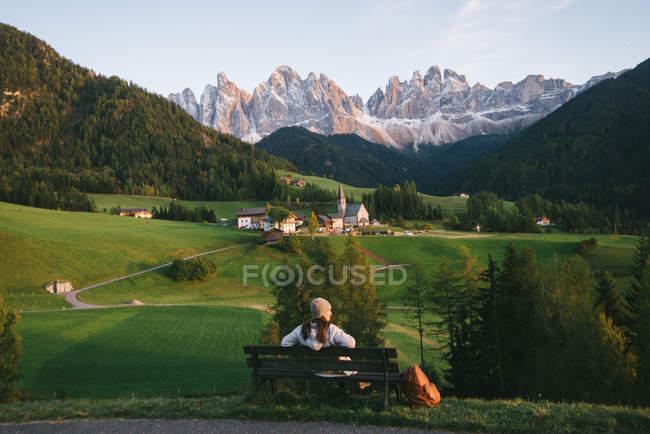 Mulher relaxando no banco do parque, Santa Maddalena, Alpes Dolomitas, Val di Funes (vale de Funes), Tirol do Sul, Itália — Fotografia de Stock