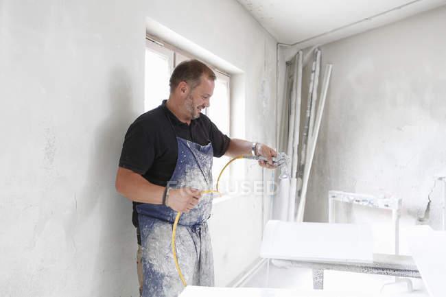Hombre rociando pintura sobre madera en taller - foto de stock