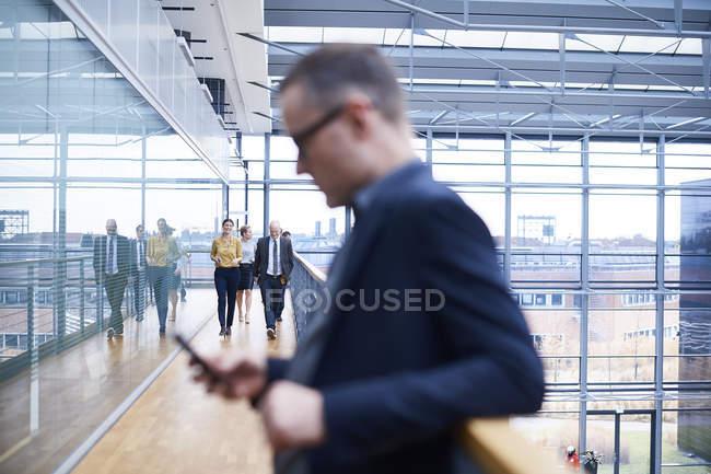 Geschäftsmann schaut auf Smartphone auf Bürobalkon, Menschen zu Fuß auf Hintergrund — Stockfoto