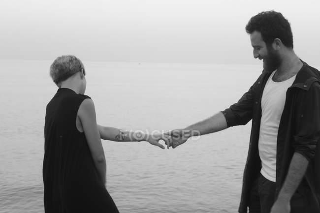 Junges paar stand neben Meer, Hand in Hand — Stockfoto