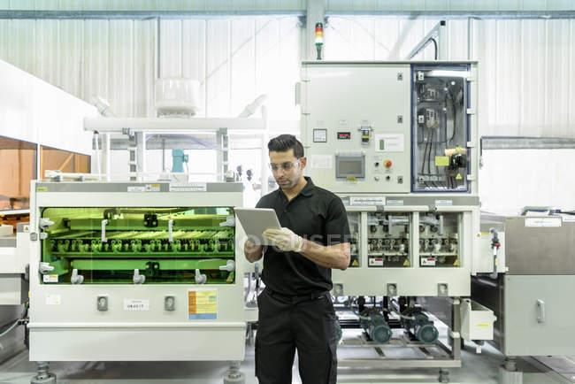 Ouvrier utilisant la tablette numérique avec la machine de traitement de circuit dans l'usine d'électronique — Photo de stock