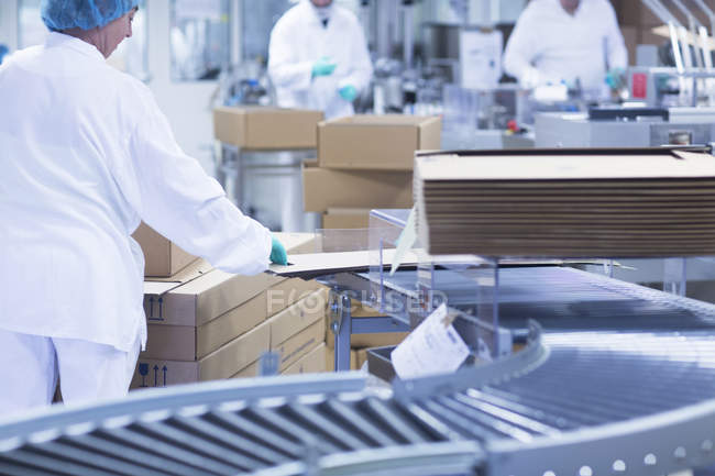 Workers packaging pharmaceutical products on production line in pharmaceutical plant — Stock Photo