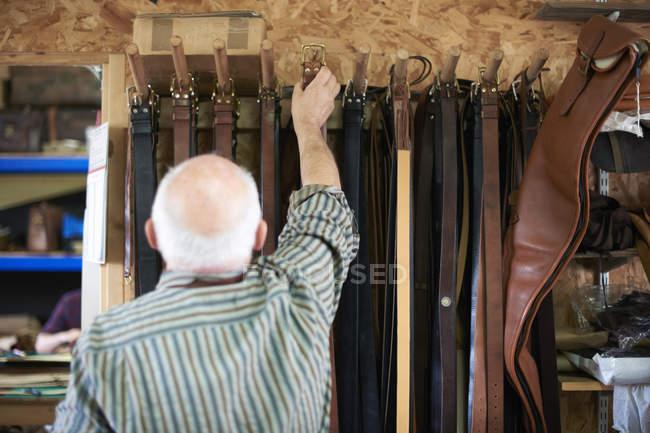 Мужского пола работника в кожевенной мастерской, висит кожаные ремни на стойку, вид сзади — стоковое фото