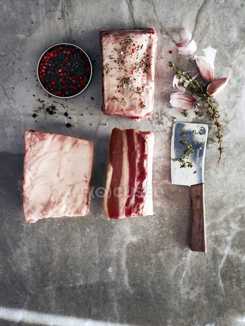 Costillas cortas de ternera cruda con cuchilla de carne y granos de pimienta, vista superior - foto de stock