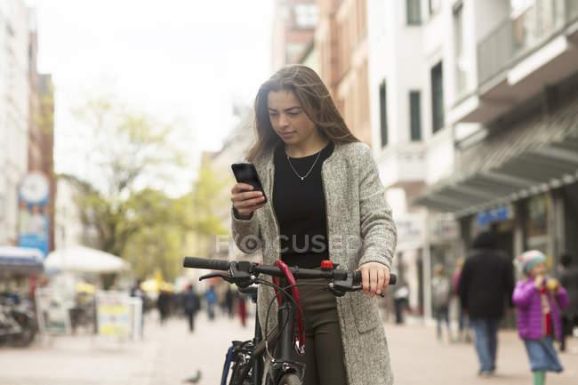 Femme parcourant le téléphone portable tout en restant avec le vélo dans la rue de ville — Photo de stock