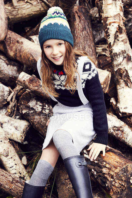 Portrait of young girl, sitting on log pile — Stock Photo