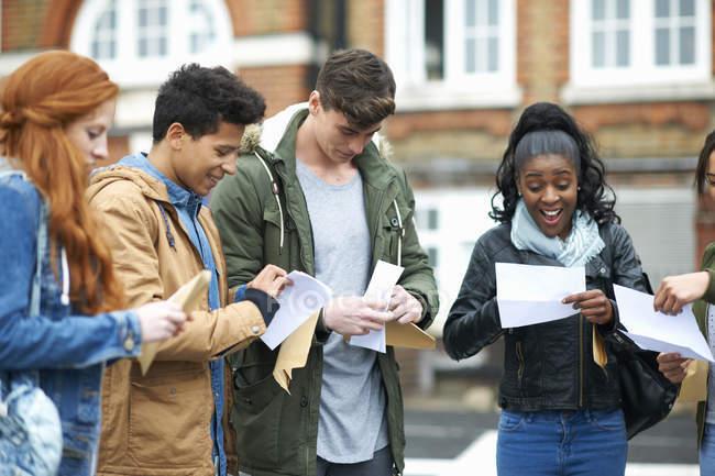 Jeunes étudiants adultes du collège lisant les résultats des examens sur le campus — Photo de stock