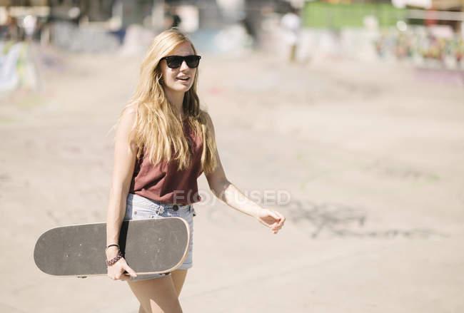 Junge Frau zu Fuß mit Skateboard im skatepark — Stockfoto