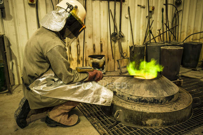 Male foundry worker taking temperature of furnace in bronze foundry — Stock Photo