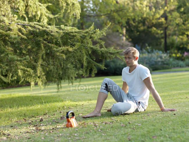 Jovem, relaxando na grama, fazendo uma pausa em exercício — Fotografia de Stock