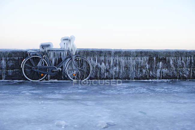 Bicycle leaning against wall covered in ice — Stock Photo