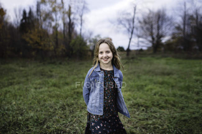 Young girl smiling in field in denim jacket, Lakefield, Ontario, Canada — Stock Photo