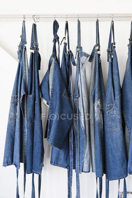 Rangée de tabliers en denim suspendus au mur blanc — Photo de stock