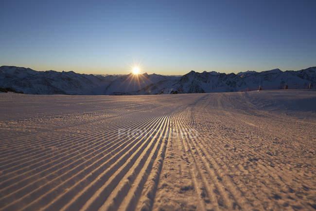 Valle dello snowy sole illuminato e gamma della montagna al tramonto — Foto stock